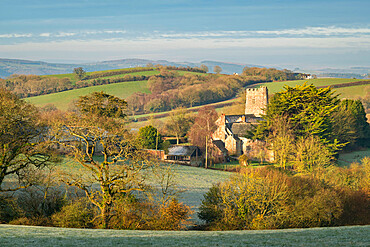 Church of St John the Baptist at Holcombe Burnell Barton, surrounded by countryside, Longdown, Devon, England. Winter (March) 2021.