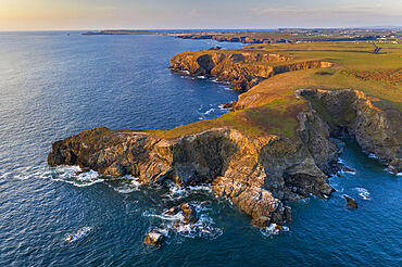 Aerial view of North Cornish rugged coastline in evening light, Park Head, Cornwall, England. Spring (April) 2021.