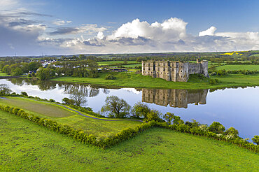 Carew Castle reflected in the mill pond on a still spring morning, Pembrokeshire Coast National Park, Wales. Spring (May) 2021.