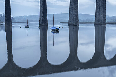 Boats moored beneath the towering arches of St Germans viaduct at dawn, St German???s, Cornwall, England. Spring (March) 2021.