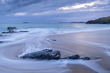 Waves wash over Mother Ivey???s Beach at dawn, St Merryn, Cornwall, England. Spring (May) 2021.
