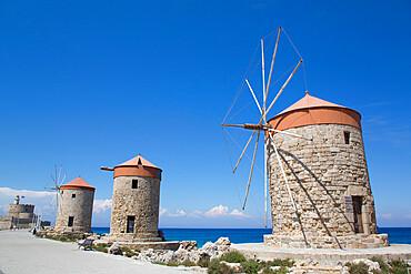 Windmills of Mandraki, Fort of St Nicholas (background), Mandraki Harbour, Rhodes, Dodecanese Island Group, Greece
