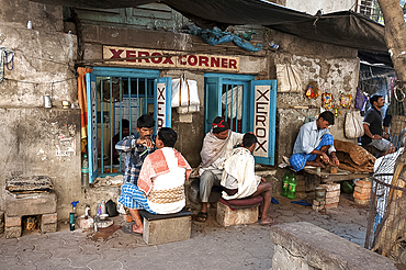 Barbers cutting hair and shaving men, and tobacco wallah, in street stalls outside Xerox shop in Dalhousie Square area of Kolkata (Calcutta), West Bengal, India, Asia