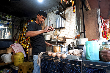 Chai wallah, pouring Indian chai into traditional hand made terracotta clay cups, in chai stall outside Kali temple, Kolkata (Calcutta), West Bengal, India, Asia