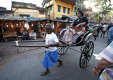 Old style running rickshaw wallah pulling woman and her shopping through Kolkata streets away from the Kali temple, Kolkata (Calcutta), West Bengal, India, Asia