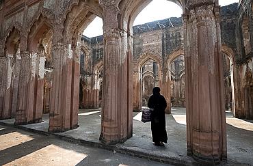 Muslim woman entering the semi-derelict 18th century Imambara and Mosque, Lucknow Residency, Uttar Pradesh, India, Asia
