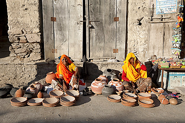 Two women in yellow and orange saris, selling hand made decorated terracotta pots and bowls, Diggi village, Rajasthan, India, Asia