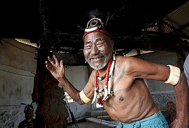 Smiling Naga man, headhunter, Wokshing Pensha, doing playful tribal dance, wearing Naga necklaces and elephant tusk arm bands, Nagaland, India, Asia