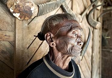 Bengshe Bengsha, elderly Naga tribal headhunter with traditional tattooed face and hair knot, Longwa village, Nagaland, India, Asia