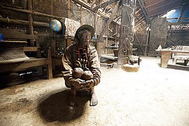 Naga man, Longsha Wangnao, head hunter, with tattooed face and Naga necklace, sitting in communal Naga tribal house, Longwa, Nagaland, India, Asia