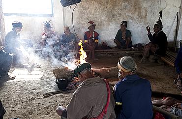 Naga men sitting chatting around the central fire in their village murung (village hall), Hongphui village, Nagaland, India, Asia