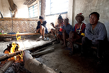 Naga men sitting chatting round fire in village muting (meeting hall), Nagaland, India, Asia