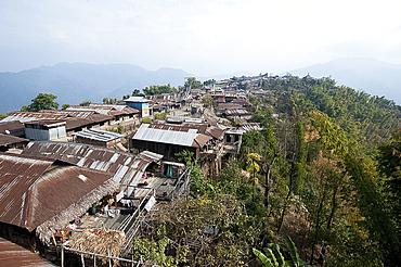 Naga village houses clinging to the hillside leading up to Baptist church at the top, Chanlangshu village, Nagaland, India, Asia