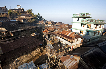 Naga village houses with bamboo stilted verandahs, clinging to the hillside, in morning light, Chanlangshu village, Nagaland, India, Asia