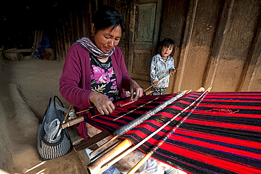 Woman weaving traditional red Naga shawl, young daughter beside her, on the verandah of the family home, Nagaland, India, Asia