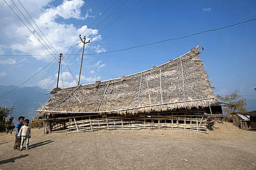 Naga children beside small bamboo constructed, fan palm thatched murung (meeting hall) with traditional curved roof, Nagaland, India, Asia