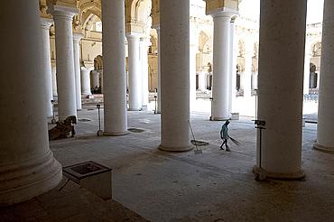 Cleaner with palm brush sweeping thousand pillar hall inside the 17th century Thirumalai Nayakkar Mahal, Madurai, Tamil Nadu, India, Asia