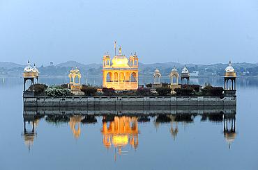 Vijay Raj Rajeshwar temple, reflected in the Gaibsagar Lake, built in 1923, lighting up at dusk for evening prayers, Dungarpur, Rajasthan, India, Asia