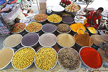 Woman in red sari at village street market stall selling spices, seeds and pasta, Chhota Udepur, Gujarat, India, Asia