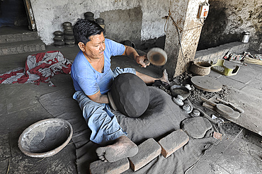Man beating hand made charcoal dusted terracotta water jar into traditional shape with a wooden paddle, Chhote Udepur, Gujarat, India, Asia