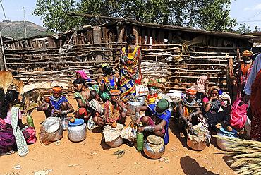 Bonda and Godaba tribeswomen selling home brewed alcohol at the entrance to weekly tribal market, Onukadelli, Odisha, India, Asia
