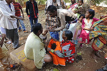 Mali tribeswoman holding hair of child having her head shaved by temple pundit at the festival of Shivraatri, Koraput, Odisha, India, Asia