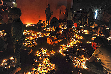 Hindu devotees placing lit puja lamps in temple courtyard to celebrate annual festival of Shivraatri, Koraput district, Odisha, India, Asia
