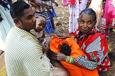 Mali tribeswoman holding hair of child having had her head shaved for choula, at the festival of Shivraatri, Koraput, Odisha, India, Asia
