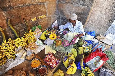Man preparing puja offerings from flowers, coconuts and fruit in 11th century Brihadisvara temple, Thanjavur, Tamil Nadu, India, Asia