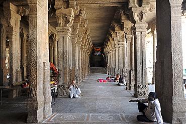 People resting in the stone pillared corridor inside the 11th century Brihadisvara Cholan temple, Thanjavur, Tamil Nadu, India, Asia