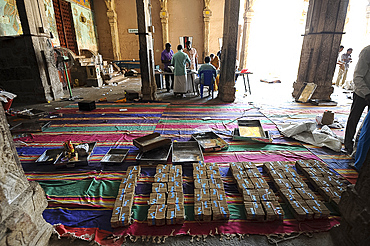 Donations of rupees being sorted, counted and bundled inside the 11th century Brihadisvara Cholan temple, Thanjavur, Tamil Nadu, India, Asia