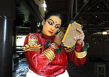 Performer carefully applying make-up with bamboo stick for a Kathakali dance performance of folk mythologies, Nilambur, Kerala, India, Asia