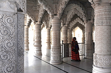 Hindu woman in red sari inside the ornate white marble Swaminarayan Temple, built following the 2001 earthquake, Bhuj, Gujarat, India, Asia