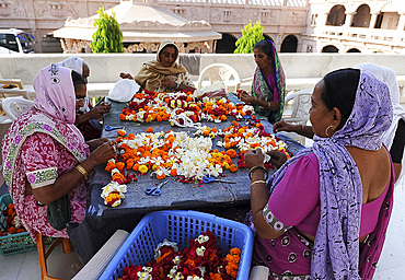 Women threading mala (garlands) for Diwali puja in the ornate white marble Swaminarayan Temple, Bhuj, Gujarat, India, Asia