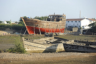 Almost completed ocean going dhow under construction at low tide, handmade from Sal wood on the Rukmavati River, Mandvi, Gujarat, India, Asia
