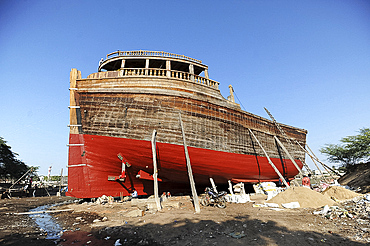 Man putting finishing touches to ocean going dhow at low tide, hand made from Sal wood on the Rukmavati River, Mandvi, Gujarat, India, Asia