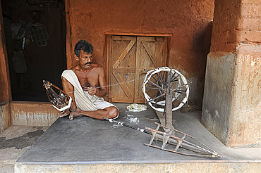 Man on his porch, spinning silk using traditional wooden spinning wheel and stick cages, Nuapatna, Odisha, India, Asia