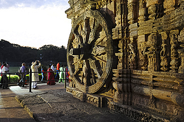 Tourists at sunset by of the 24 carved huge stone chariot wheels carved on 13th century Konark Sun Temple, UNESCO World Heritage Site, Odisha, India, Asia