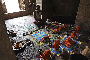 Priest arranging puja ceremony inside 7-8th century Parashurameshvara Temple, Bhubaneswar, Odisha, India, Asia