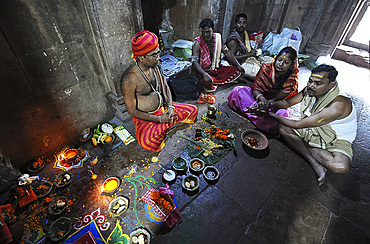 Priest performing puja ceremony with couple inside 10th century Mukteswar Temple, Bhubaneswar, Odisha, India, Asia