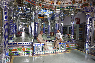 Two men sitting in ornately decorated Jain temple in backstreet, Udaipur, Rajasthan, India, Asia