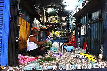Two men in Malik Ghat flower market threading floral garlands, Kolkata, West Bengal, India, Asia