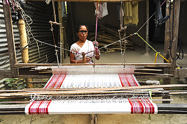 Village woman with domestic handloom, weaving a traditional Assamese cotton gamosa, white with red borders, Assam, India, Asia
