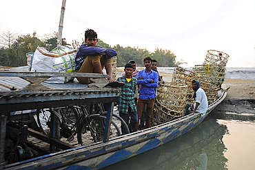 Village men with baskets and bicycles, on the local village ferry waiting to cross the Brahmaputra river, Assam, India, Asia