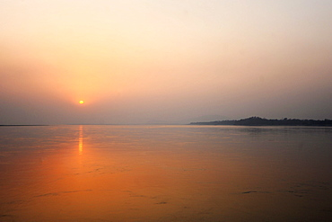 Sun setting over the vast waters of the mighty Brahmaputra River, Assam, India, Asia