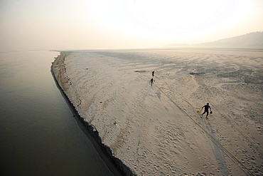 Three men at sunrise releasing ropes from a mooring in the fine sand of a seasonal sandspit, Brahmaputra River, Assam, India, Asia
