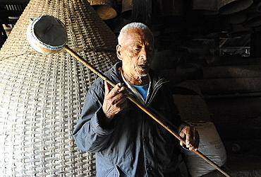 Naga elder playing domestic stringed gourd and bamboo instrument and singing, Phek, Nagaland, India, Asia