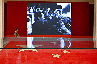 Museum visitor walking past party political slideshow in the National Museum of China, Beijing, China, Asia