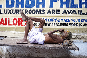 Holy man (Saddhu) resting on a marble slab, Udaipur, Rajasthan, India, Asia