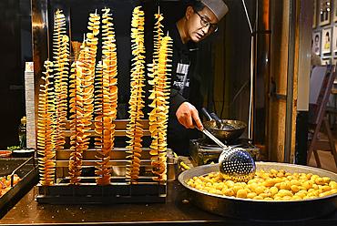 Man cooking fried spiralled potato on long sticks for sale in Muslim quarter night market, Xian, Shaanxi, China, Asia